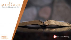 An open Bible on a wooden table with a blurry background of a stone wall