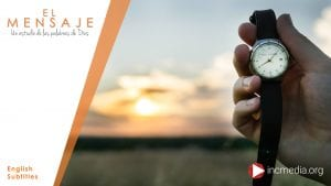 Hand of a person holding a watch with leather banding in front of a distant sunset with clouds