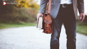 man wearing a suit with a bible and bag