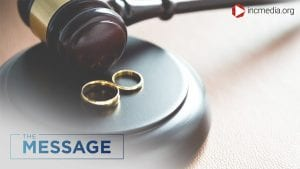 Two wedding rings next to a gavel and on a block.