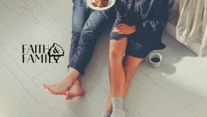 Husband and wife sitting on the bedroom floor eating breakfast