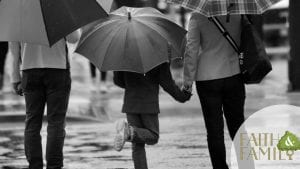 Parents standing next to a child under umbrella in the streets