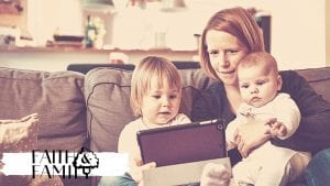 Mom on the couch with her toddler and baby looking at the ipad