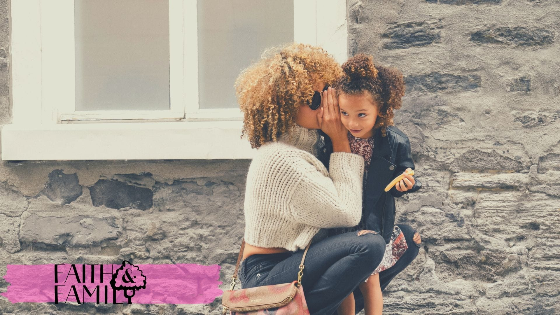 Mom whispering to her daughter toddler while kneeling down to her level.