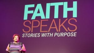 """woman speaking on stage with text on the big screen behind her: """"Faith Speaks - Stories with Purpose"""""""