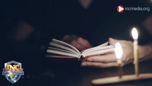 person holding an open book with two candles in front