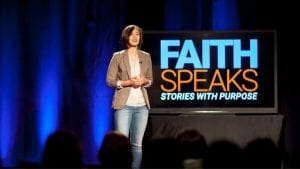 """Woman speaking on stage with """"Faith Speaks"""" in the background"""