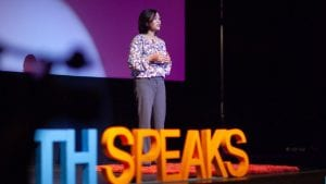 A woman stands on stage to tell her story