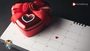 calender with february 14 marked with a heart and a heart shaped box of chocolates on top of the calendar