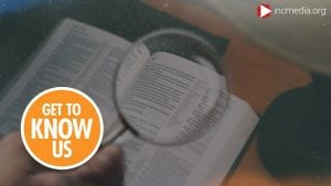 A hand holding a magnifying glass over an open Bible on a table.