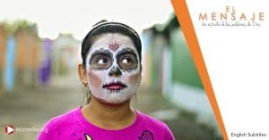 A girl in a bright pink shirt wearing face paint like a skull standing outside next to colorful painted houses.