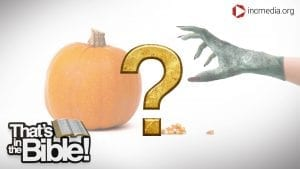 A gold question mark in front of hand wearing a costume glove outstretched towards a pumpkin and candy corn.