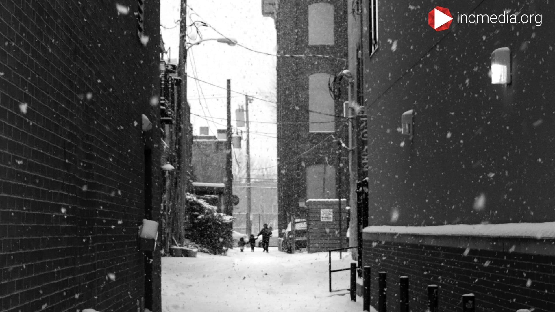 Alleyway with snow falling, a mom carrying three kids in the distance.