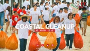 """Volunteers carrying bags of garbage with text overlay: """"Coastal cleanup, Atlantic Coast"""""""