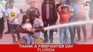 Fireman assisting a little girl in holding a fire hose spewing water.