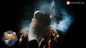 A priest, surrounded by smoke, holding a crossier amongst a crowd of worshippers raising their hands in the dark.