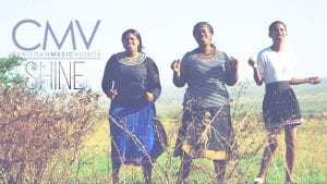 """Three African women with traditional face painting singing in field with text overlay: """"Shine"""""""