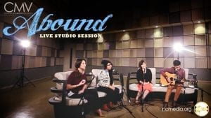 """Group of singers in studio sitting on couches with text overlay: """"Abound Live Studio Session"""""""