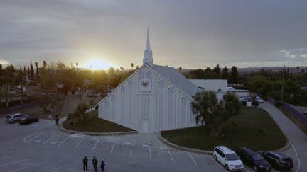 Birds eye view of the exterior of the house of worship with the sunset in the background.