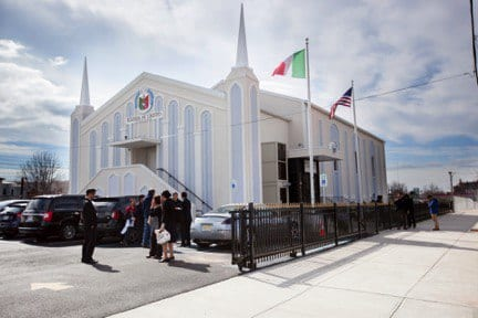 Exterior of Jersey City house of worship with a group of people standing outside on a clear day.