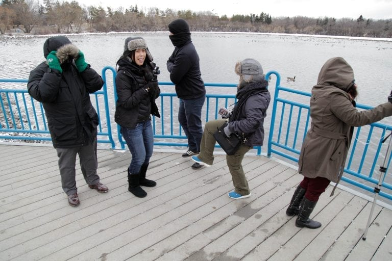 Production crew in outer winter wear jumping around outside trying to stay warm.