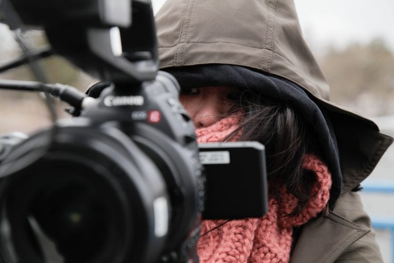 Close up of camera woman's face covered up in order to stay warm with a camera in front of her face.