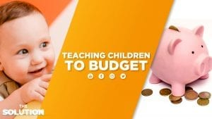 A baby smiling and a piggy bank surrounded by coins with text overlay Teaching Children to Budget.