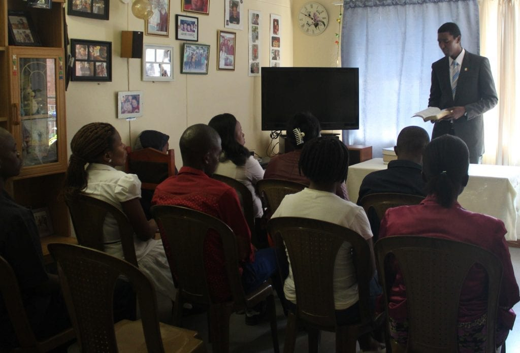 minister preaching to south africans in a home