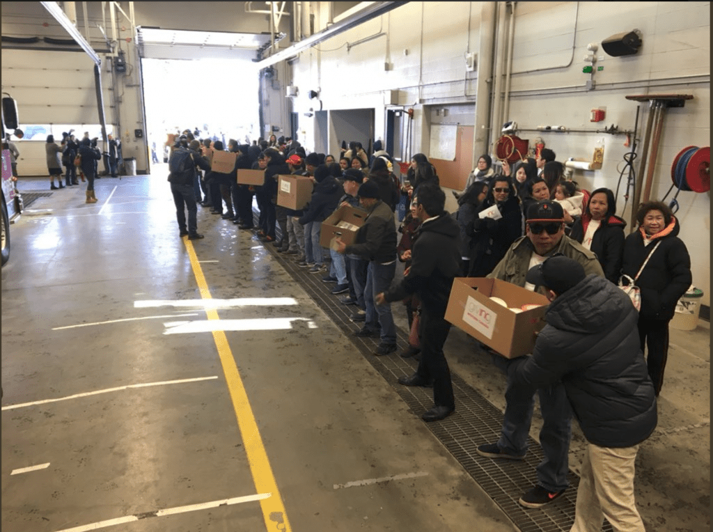 """assembly line of people passing boxes of donations with """"INC Giving"""" written on boxes"""