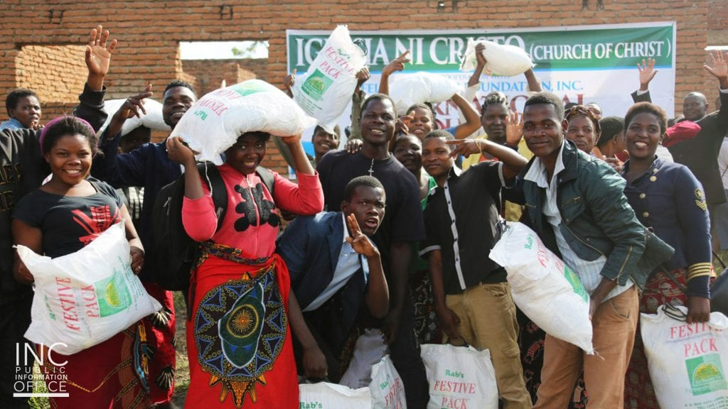 people from Malawi and Kenya smiling holding bags of food parcels