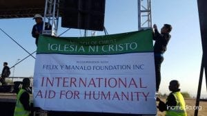 People hanging banner of International Aid for Humanity