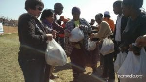 People receiving relief goods in white plastic bags