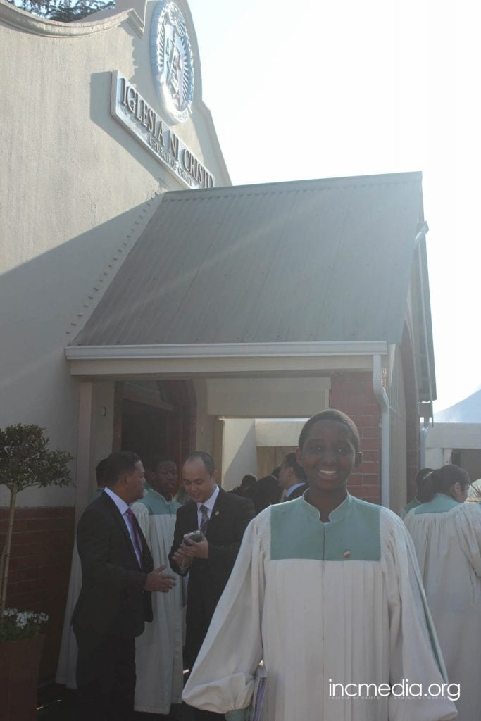 South African person in choir robe in front of worship building.