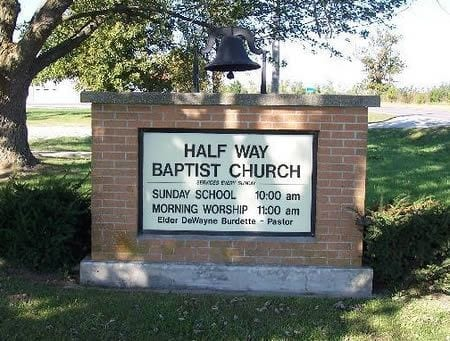 A park setting with brick wall signage that reads Half Way Baptist Church