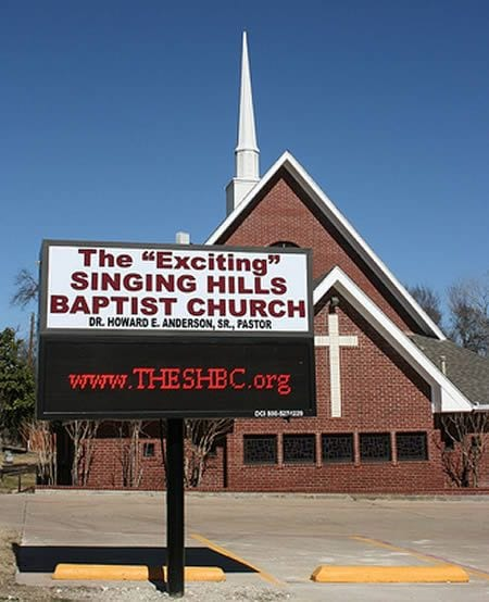 """A sign in front of a chapel that says The """"Exciting"""" Singing Hills Baptist Church"""
