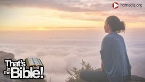 Woman sitting on the edge of a cliff, above the clouds, facing a sunset