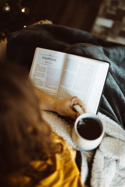 Girl reading Bible with cup of coffee.