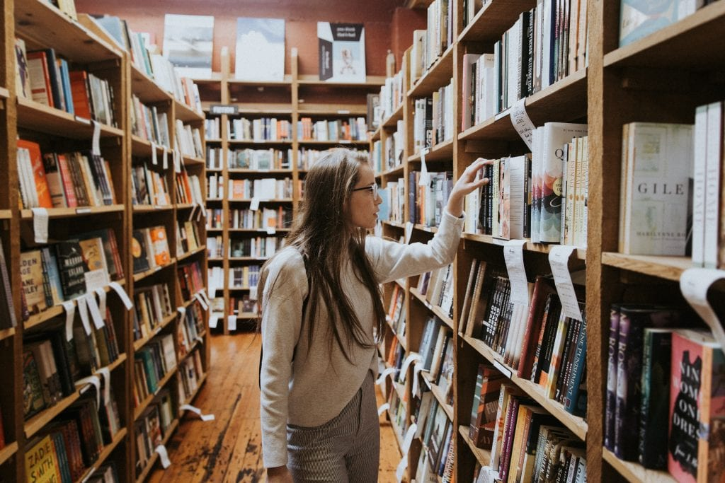 Girl looking at books at bookstore.