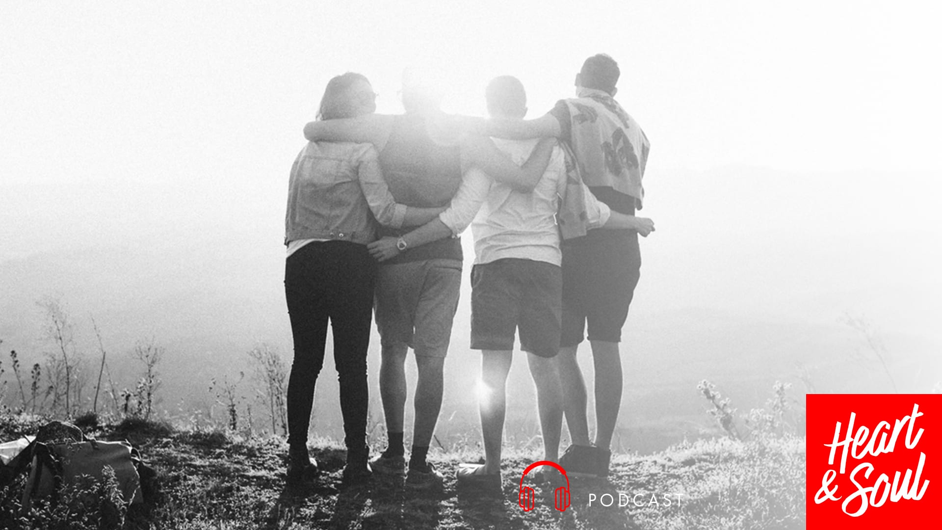 black and white picture of 4 people turned around, with arms around each other