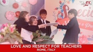Teachers and students on stage presenting award
