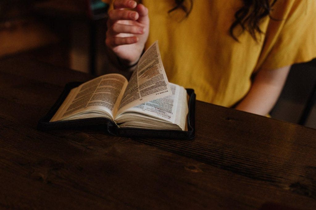 A bible on top of a table with it open and a woman flipping through the pages.