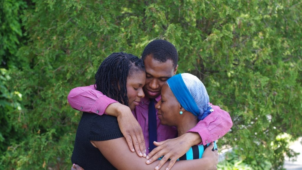 Son embraces mom and sister with a green shrub in the background.