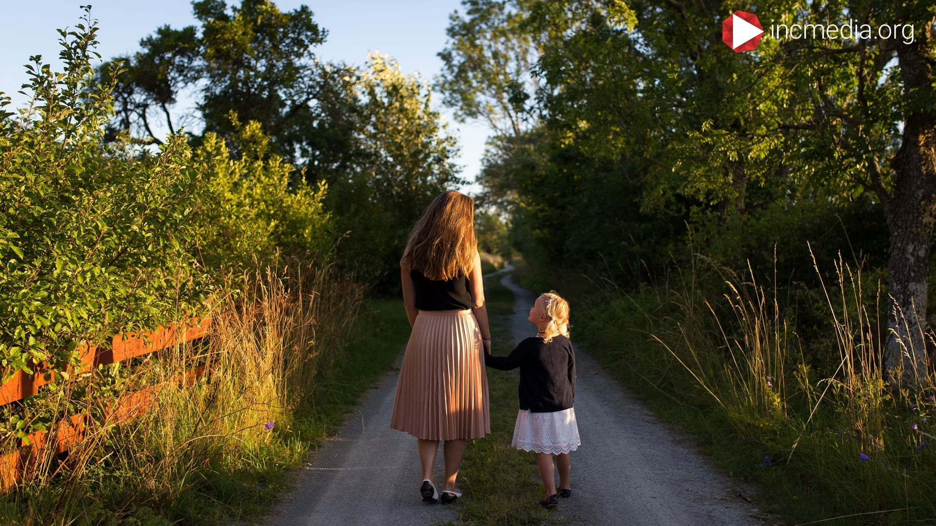 Mom and daughter walking down a path surrounded by trees