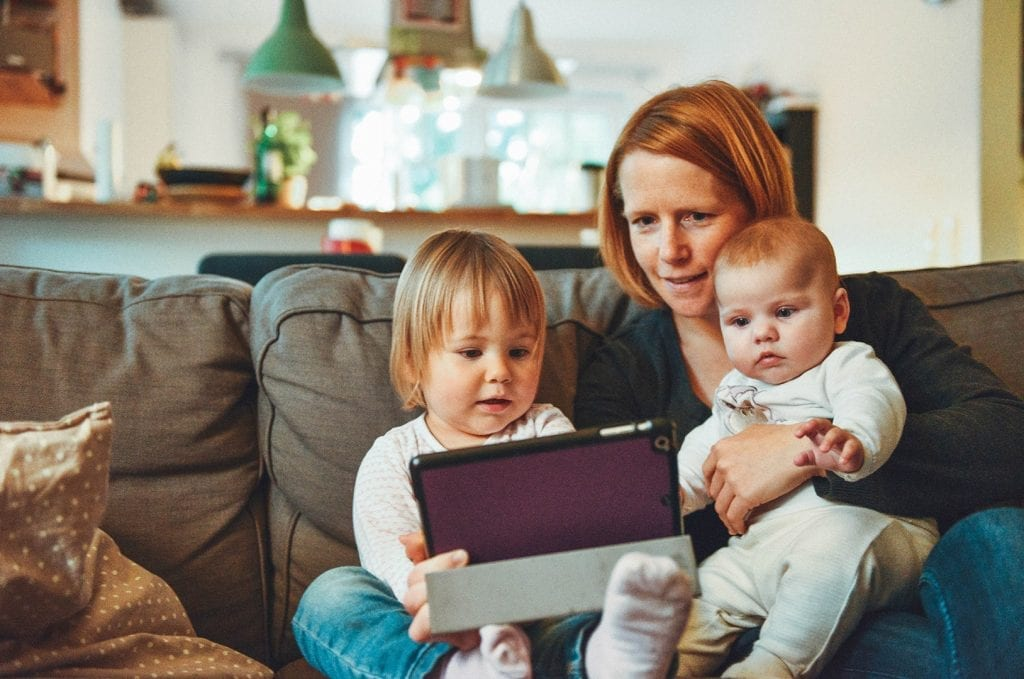 Mom with two kids watching a tablet while sitting on a couch.