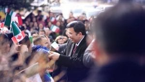 The Executive Minister is met by a young boy standing in a crowd of people.