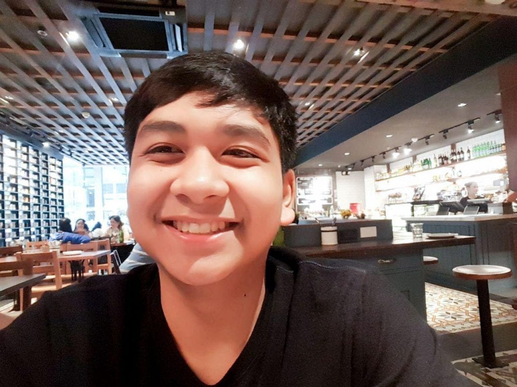 A young man smiling in a restaurant.