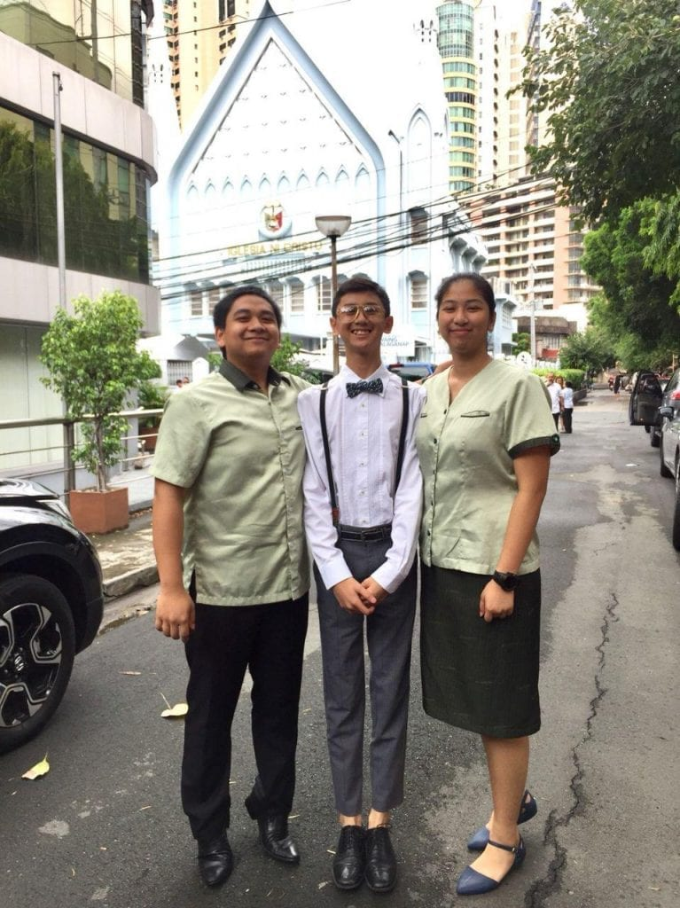 A group of 3 young people standing on the street with an INC house of worship behind them.