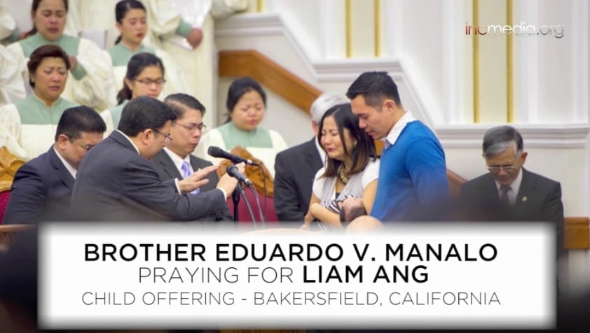 A couple holds their newborn son who is being prayed over by the Executive Minister.