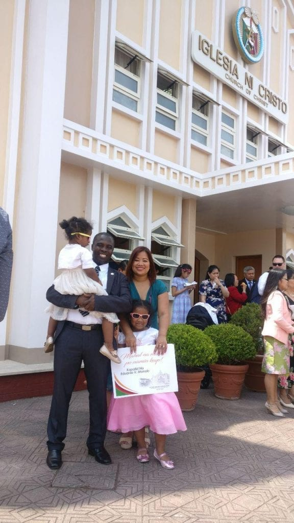 A family of 4 posing in front of the Church Of Christ House of Worship in Rome, Italy.
