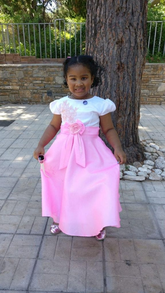 A girl in a pink and white dress showing off her fancy clothes.